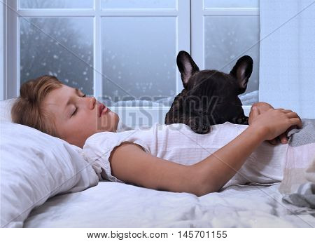 The young girl the teenager and a dog sleeping in the bed. Sound sleep early morning. Winter the snow outside the window