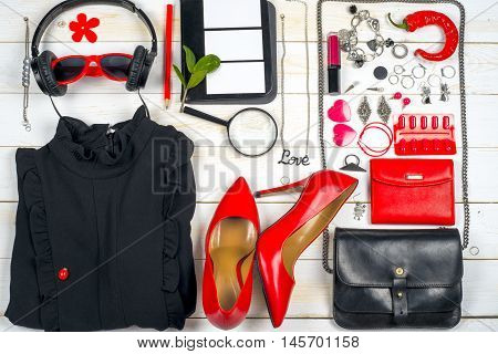 Women clothing set and accessories on white wooden background. Red and black. Top view