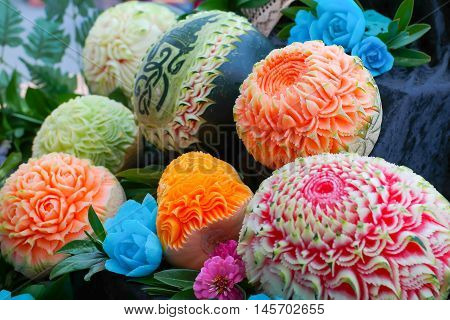Colorful fresh carved pumpkins and melons: fruit carving or food sculpture