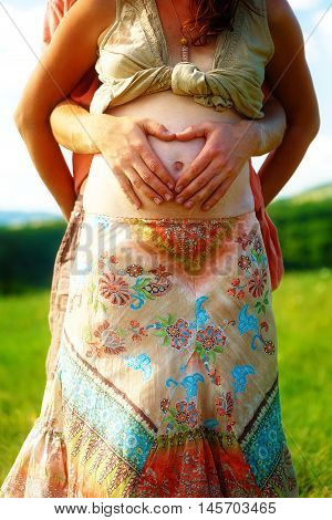 Loving beautiful ethno couple, man makes the heart shape on her pregnant belly