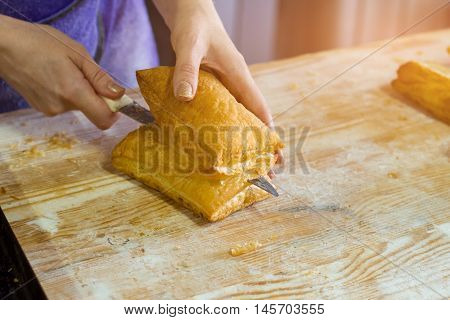 Hand with knife cuts puff. Pastry on wooden board. Baker in the kitchen. Fresh and airy dough.