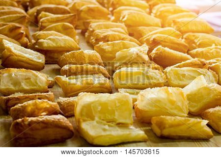 Puffs on wooden board. Yellow pastry under sunlight. Early morning at the bakery. Product made of dough.