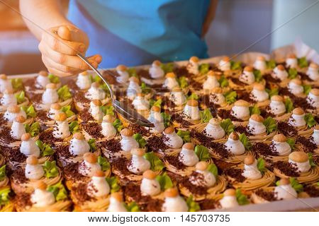 Desserts with chocolate crumbs. Female hand holding a spoon. Confectioner at the cafe. How to create special taste.