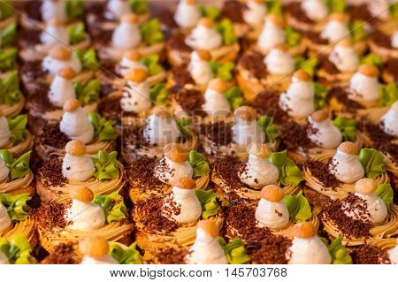 Small cakes with chocolate crumbs. Desserts decorated with cream. Sweet treats at holiday party. Guests will be pleased.