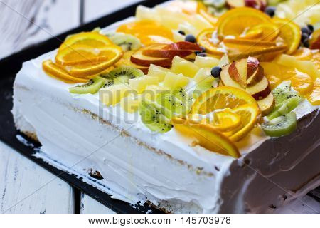 White cake with fruit pieces. Slices of kiwi and orange. Expensive custom made cake. Festive dessert in a restaurant.