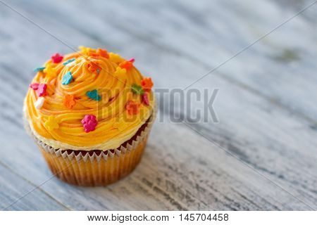 Decorated cupcake on gray surface. Dessert with orange cream. Improve appetite and lift mood. Pastry that's worth trying.