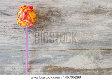 Glazed candy on a stick. Cake pop with bright icing. Mix of positive colors. Find occasion for joy.