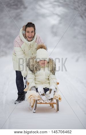 Mom rolls her daughter on a sled in winter park