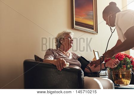 Home Healthcare Nurse Checking Blood Pressure Of Senior Woman