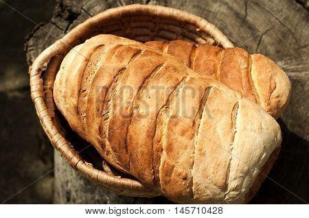 Bread in a wicker basket on the stump closeup
