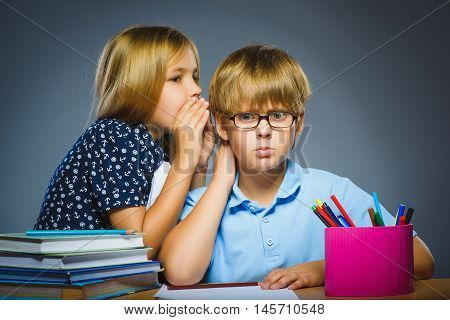 girl whispering in the ear of Teenager or boy on gray background. Communication concept.