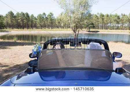 Young wedding couple in blue cabriolet car in front of river