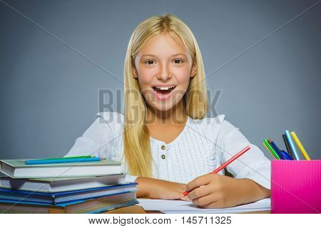 school concept. Closeup portrait successful happy girl draws pencil on gray background