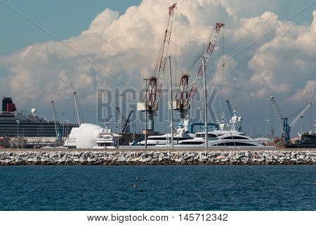 Cranes at Work in Boatyard near Lighthouse