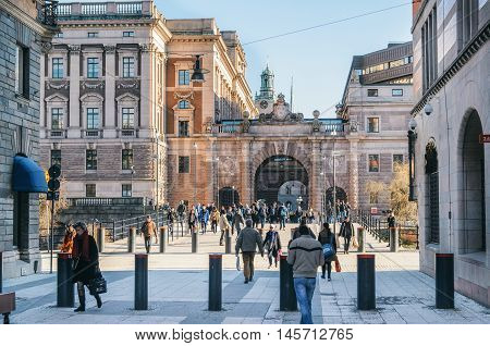STOCKHOLM SWEDEN - MARCH 18 2015: People walk on Drottninggatan or Queen Street on a background Of the Arch of parliament Riksdag.