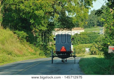 Back view of Amish horse and buggy on the road in rural Lancaster county Pennsylvania