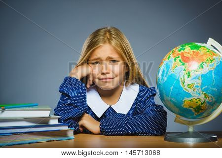 school concept. crying girl with astonished or doubt expression sitting at desk.