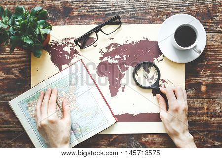 world map on a wooden table time to travel with girl hands