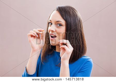 Young woman is using dental floss. Dental hygiene concept.