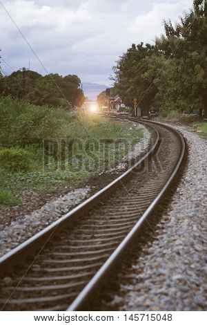the curve of railway near train station with tree at left and right side of railway,vintage filtered image light and flare effect added selective focus,local train station,thailand