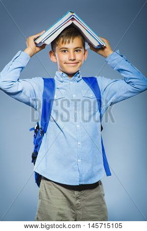 school concept. portrait successful happy boy with knapsack holding book on his head.