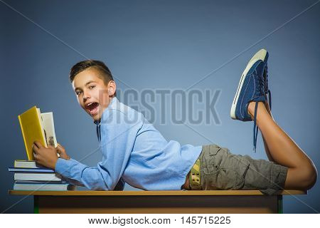 school concept. Boy lying on the desk and reading a book.