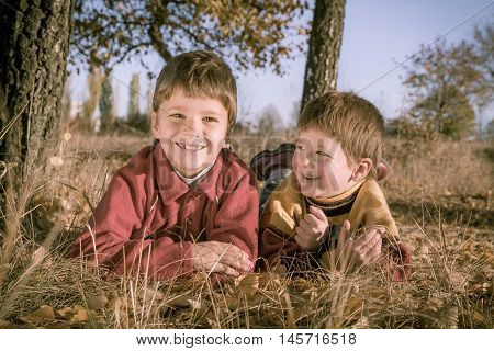 Two smiling boys lying down on withered grass in autumn park, sepia toned image