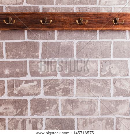 A row of hooks for clothes on the brick wall