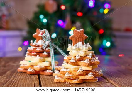 Home made baked Christmas gingerbread tree as a gift for family and friends on wooden background. With colorful lights from Christmas tree on background. With icing sugar als snow. Selfmade gift for xmas.
