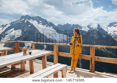 Child drinking warm tea in the rustic wooden outdoor cafe on mountain, alpine view, snow on hills. Dombay, Karachay-Cherkessia, Caucasus, Russia.