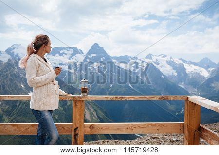 Woman drinking warm tea in the rustic wooden terrace on mountain, alpine view, snow on hills. Dombay, Karachay-Cherkessia, Caucasus, Russia.