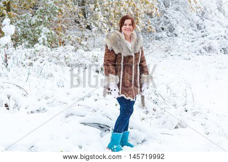 Young beautiful woman having fun with snow outdoors on beautiful winter day. Girl in fashon winter look walking through park during snowfall