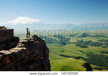 Two travelers father and child standing on top of Bermamyt plateau and looking on Elbrus mountain. Karachay-Cherkessia, Caucasus, Russia.