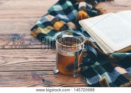 Mug with tea bag, book and plaid winter blanket on vintage wooden table