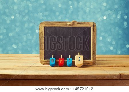 Jewish Holiday Hanukkah background with wooden dreidel spinning top and chalkboard over blue bokeh lights