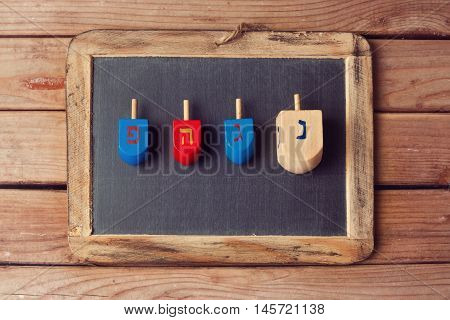 Jewish Holiday Hanukkah background with wooden dreidel spinning top and chalkboard