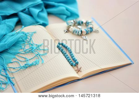 A blank notebook with a blue cover lies on a white background. At the turn of the notebook are 2 bracelets in a marine style, and around it a blue scarf with fringe