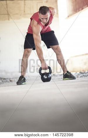 Young muscular athletic built man working out lifting a kettlebell weight in an abandoned ruined building