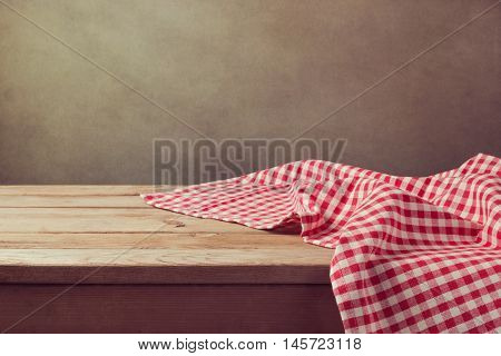 Empty wooden deck table with checked tablecloth for product montage display