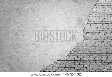 White brickwork underneath concrete wall. Textured suface. Half painted wall. Background. Cracks and roughness.