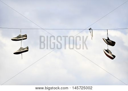 Two pairs of shoe laying on an electricity cable with blue sky on background