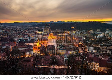 Aerial view of Ljubljana Slovenia city center. Illuminated old buildings. Mountains at the background