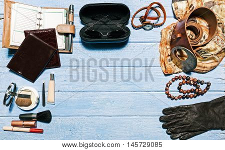 Contents of modern woman bag: female accessories on the blue planked surface. Flat lay