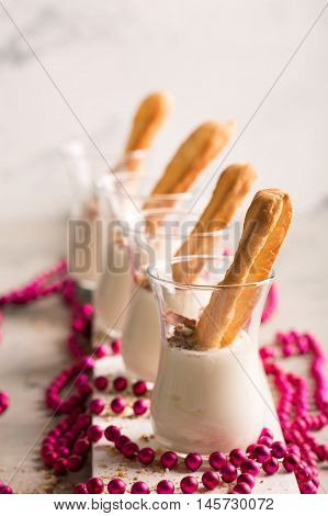 Sweet Tasty Eclair with white sauce. Small cakes into glasses with cream