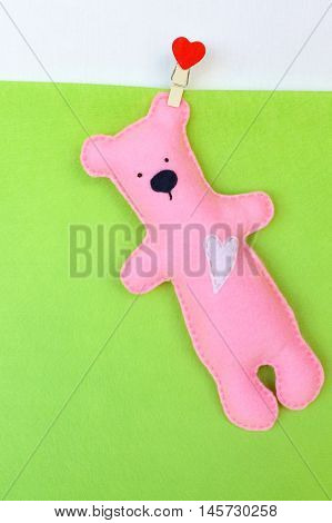 Felt bear toy. Pink felt bear on green background, hand stitched toy