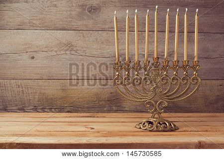 Traditional Menorah with candle lights on wooden table