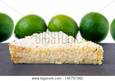 Lemon lime coconut impossible pie with white chocolate shavings slice on a gray slate with limes in the background