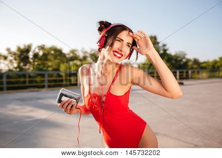 Young smiling brunette girl listening music with headphones and old mp3 player