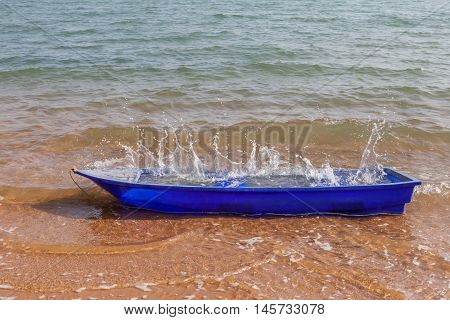 Blue rowboat with splashing water on the beach coastline.
