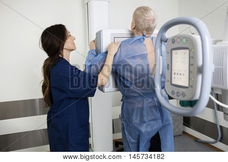 Mature Radiologist Taking Xray Of Man In Hospital